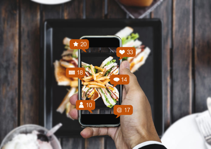 Taking food photograph by mobile smart phone, and sharing on social media, social network with notification icons